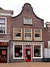 foto van Huis met ingezwenkte halsgevel met vernieuwde halfronde gemetselde top