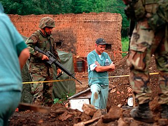 Kosovo Force - U.S. Marines provide security for Royal Canadian Mounted Police officers as they investigate a mass grave in July 1999.