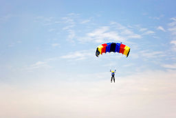 Red, yellow and blue parachute against cloudy sky (5278205683)