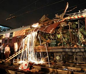 2006 Mumbai train bombings - Railway workers cutting a damaged part of the bomb-damaged coaches