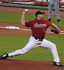 "A man in white pants and a maroon baseball jersey with ""ASTROS 22"" on the chest pitches a baseball with his right hand."