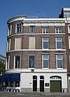 foto van Herenhuis op de hoek van de Zeemanstraat, met gepleisterd souterrain en drie verdiepingen. Geprofileerde cordonlijsten en kroonlijsten met consoles