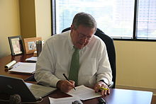 A grey-haired man with a white shirt and green tie sits at a desk in front of an open window, looking down to follow his pen as he writes on a sheet of paper