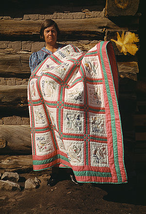 Patchwork quilt - Mrs. Bill Stagg of Pie Town, New Mexico with her embroidered patchwork quilt that displays all 48 (at the time) United States state flowers and birds, October 1940.