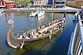 Saga Oseberg viking ship replica Tønsberg Norway Young students rowing Byfjorden Harbour havn Brygga pier board walk Aft Stern akter Rudder ror Tønsbergs Blad sailboat View from Kaldnes bro footbridge 2019-08-26 blurry faces 5125.jpg