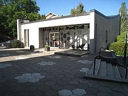 Kirkens entrégitter blev tegnet af kunstneren Berndt Helleberg.   Jordbelægningen består af sekskantede betongstenplader som danner slagsen blomster.   Trapper og afsatser er i granit, jordbelægningen har også indslag af småbrosten placerede i rækker.