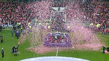 Confetti rains around a platform in the middle of a football pitch