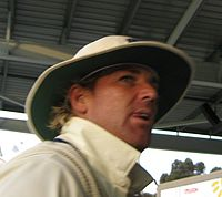 A man in cricket whites and hat. He is standing on steps of a stand.