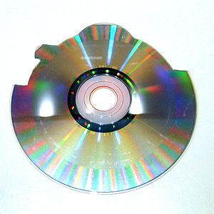 Shaped Compact Disc - Picture of the back of a shaped CD. This CD was produced as a round disc and automatically cut to shape using a computer aided machine with a rotary tool. It's easy to distinguish that the data track of the disc is smaller compared to a full 72 minute disc; it ends before it reaches the outside border of the disc to allow the unused media on the outside to be cut away.