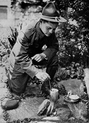 A SOLDIER BOILING HIS RATION OVER THE HOME-MAD...