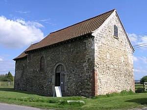 A simple stone church seen from the northeast with a tiled roof, a nave with a round-arched doorway and, beyond, a smaller chancel