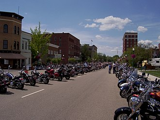 "Poker run - Street lined with motorcycles at a rally in Marietta, Ohio which incorporates a ""Ride for the Red"" dice run benefiting the American Red Cross."