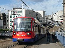 A Sheffield Supertram in current blue, orange and red Stagecoach livery. The tram shown is crossing Park Square bridge and Fitzalan Square and Castle Square can be seen in background, as can tram tracks and numerous commercial buildings.