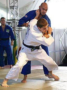 Judoka practicing tai otoshi throw in Judo class