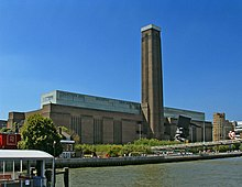 A large oblong brick building with square chimney stack in centre of front face. It stands on the far side of the River Thames, with a curving white foot bridge on the left.