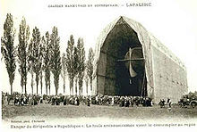 An airship inside a field hangar in centre, only the tail of the airship is visible; to the left of the hangar is a row of poplars or approximately the same height as the hangar roof. In front of the hangar a large crowd is assembled.