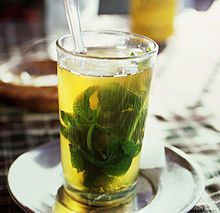 A glass with a large mint leaf floating in green tea