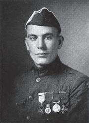 Head and shoulders of a clean cut man in military uniform with four medals hanging from ribbons on his chest and a garrison cap.