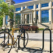 A yellow bike in front of the Tippie College of Business building, a large, white building with green trim.