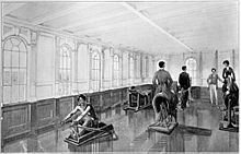 View of the interior of a brightly lit gymnasium. A man is using a rowing machine in the foreground, while a man and a woman ride exercise horse machines. Two more men are visible standing in the background.