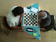 Photographie prise au-dessus de deux joueurs devant un échiquier.