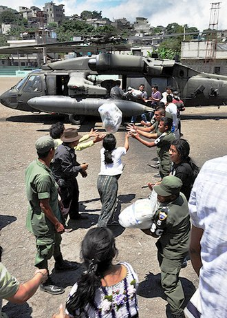 Tropical Storm Agatha - Guatemalan soldiers unloading relief supplies from a Joint Task Force-Bravo UH-60 Blackhawk
