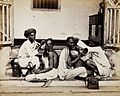 Two Indian barbers wearing turbans shaving the heads of two Wellcome V0029726.jpg
