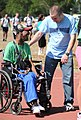 U.S. Air Force Airman Basic Andrew Meier, right, interacts with athlete Roderick Smith after they completed the 30-meter assisted slalom wheelchair race during the Mississippi Special Olympics Summer Games at 110514-F-BD983-006.jpg