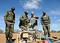 U.S. Army Sgt. David Thompson, center right, the supervisor for the tactical water purification system with Alpha Company, 405th Brigade Support Battalion, Illinois Army National Guard, assists a member with 120808-Z-VI159-034.jpg