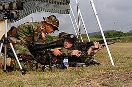 US Navy 050627-A-2545J-007 U.S. Army Reserve Sgt. Maj. Robert Payne, left, instructs U.S. Navy Midshipman Jake Rankinen on proper body positioning during live fire marksmanship training