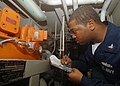 US Navy 050713-N-4374S-002 Gas Turbine System Technician 3rd Class Travis Buchanon logs a reading from a hydraulic oil power module for a control reversible pitch propeller in Main Engine Room Two.jpg
