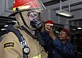 US Navy 090410-N-9520G-047 Information Systems Technician 2nd Class Shana Gibbs, from Chicago, Ill., adjusts a Sailor's firefighting gear during a general quarters drill.jpg