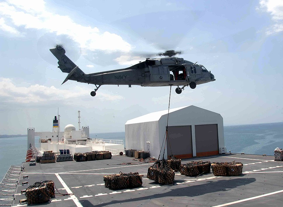 US Navy 090414-F-4455C-004 An MH-60S Sea Hawk helicopter carries one of the 333 loads of cargo from the Military Sealift Command hospital ship USNS Comfort (T-AH 20) as the ship is anchored offshore near Port-Au-Prince