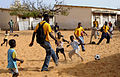 US Navy 100409-N-7948C-027 Boatswain's Mate Seaman Jean Petitfrere plays soccer with children during a community outreach project at Pikine17A and HLM Pekine grade school.jpg