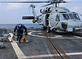 US Navy 110311-N-5324W-117 Boatswain's Mate Seaman Tyler Behrens removes the chocks and chains from an SH-60B Sea Hawk helicopter assigned to the V.jpg
