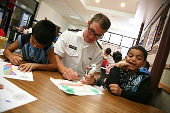 US Navy 110906-N-YM440-141 Midshipman 3rd Class Jonathan Larson, a Navy ROTC member at the University of Nebraska, draws with students at Everett E.jpg