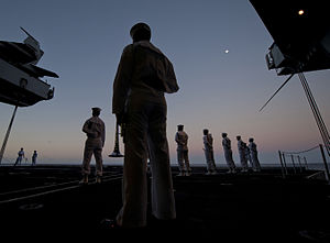 US Navy 111213-N-DR144-035 Sailors assigned to a burial detail wait to begin a burial at sea ceremony for 22 former service members at dawn aboard.jpg