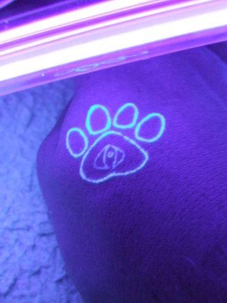 UV tattoo - UV tattoo on a hand illuminated under a blacklight.