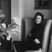 slim, middle-aged white woman, elegantly dressed, seated in high-backed armchair. A vase of flowers is in the foreground.