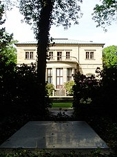 A grey slab, level with the ground framed by bushes and in the shade of the tree. In the background a fountain and a large two-storied house with a balcony.