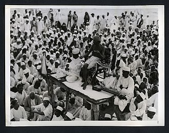 Khadi - Gandhi spins by hand while addressing his followers