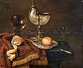 Willem Claesz. Heda - A clementine in a porcelain bowl, a nautilus cup, a roemer, two glasses, a knife, a peeled lemon on an ornamental carpet on a table.jpg
