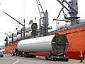 Wind turbine towers being unloaded at a port.jpg
