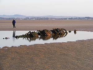 "X-class submarine - The remains of an XT-class craft on the beach at Aberlady Bay in 2008. The bow is to the left, the stern to the right. From left to right can be seen the wet and dry chamber hatch, the ""conning tower"" (the periscopes penetrated the hull through the ""eye"" shape) and the secondary hatch."
