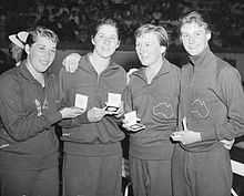 A black-and-white photograph of four young women in tracksuits holding medals in boxes