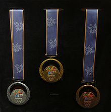 Three round medals with blue ribbons hanging in a display. The medals are silver, gold, and bronze from left to right.
