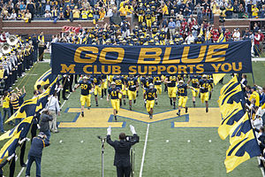 Michigan Wolverines - Michigan Marching Band salutes the 2009 Michigan Wolverines football team as it enters the field at Michigan Stadium.