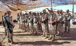 405th Air Expeditionary Wing - Air Force security forces from the 405th Air Expeditionary Wing listen to instruction during guard mount at an Operation Enduring Freedom location. A guard mount is conducted to brief security forces troops before a shift change.