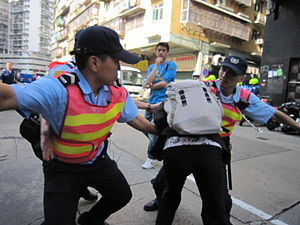 Public Security Police Force of Macau - PSPFM officers restrain a protestor during May 1, 2010 protests in Macau.