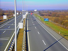 A view of the motorway from a flyover, a variable traffic sign gantry is visible